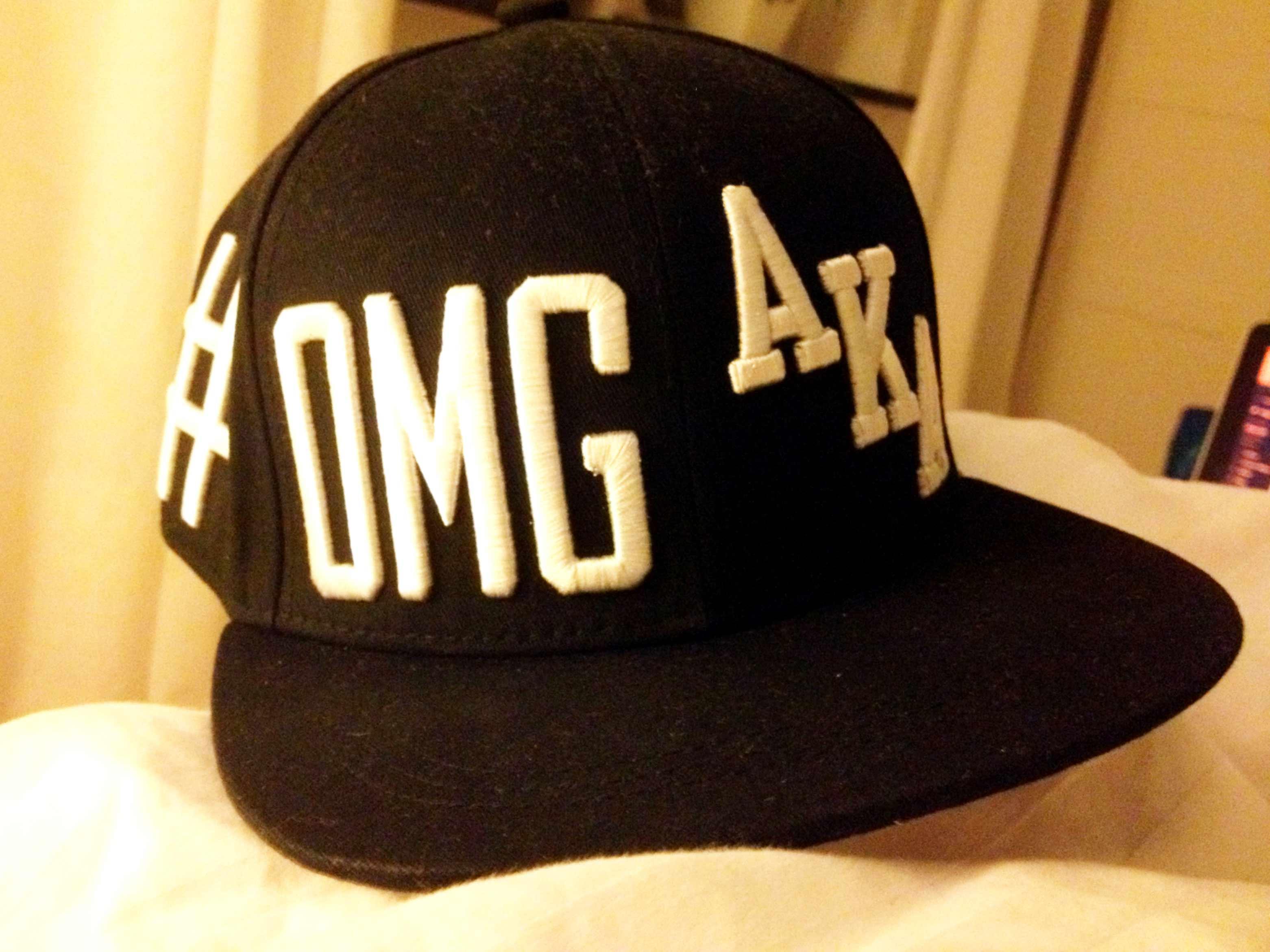 En svart keps med bokstäverna OMG och AKA.