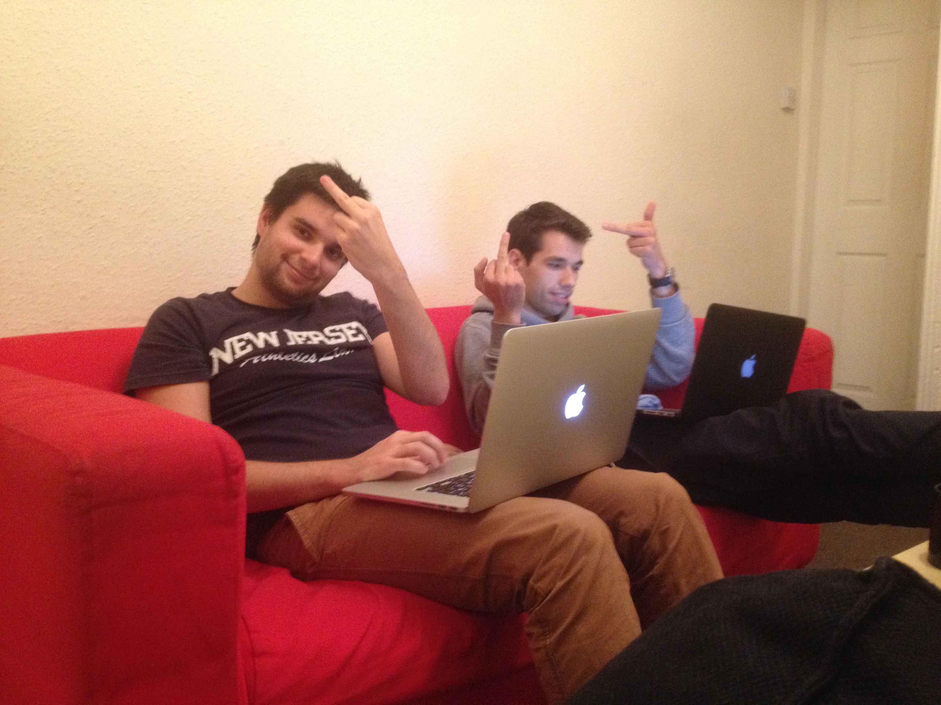 Två personer i en soffa som räcker fingret åt kameran.