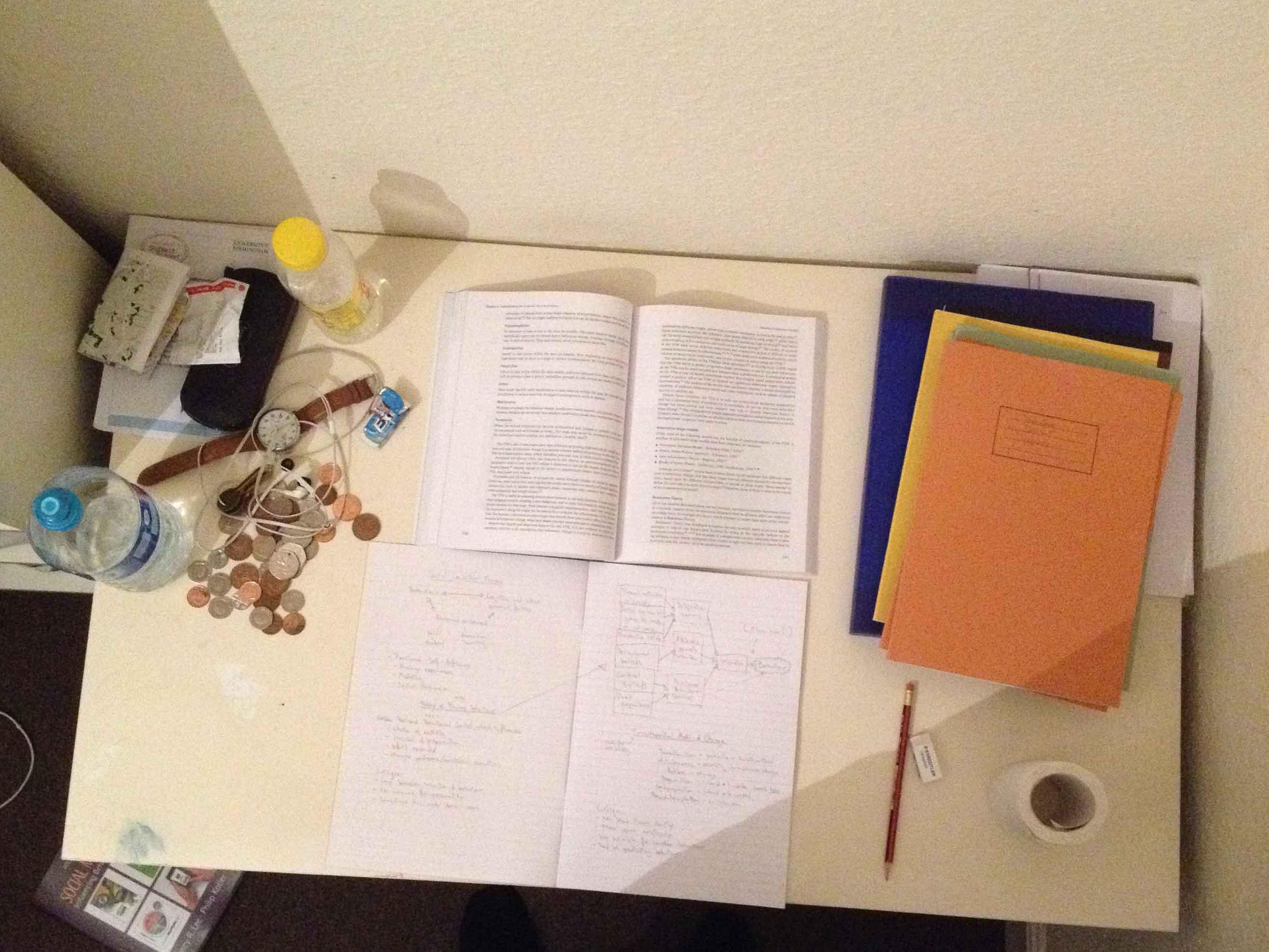 Ett skrivbord med en bok och anteckningsböcker.