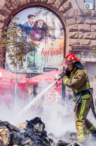 Brandmän släcker eld i kaoset vid Coca colas reklamtält.  Foto: Daniel Kindstrand.
