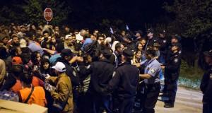 Poliser bildar en kedja framför flyktingar som vill från Serbien till Kroatien. Foto: Daniel Kindstrand