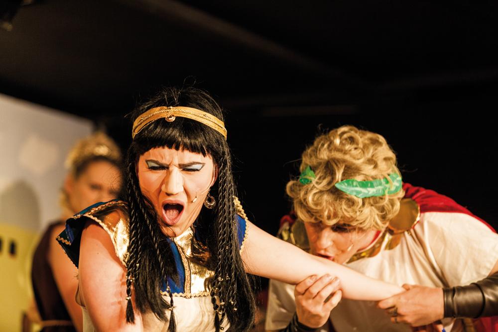 """KRISCHANSTASPEXET. I takt till publikens jubel kysser, och slickar, Julius Caesar den äcklade Kleopatras arm. Caesars charm har inga gränser; publiken skanderar """"en gång till, en gång till""""!"""
